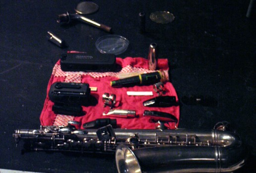 An alto saxophone lying on a red cloth along with various small objects