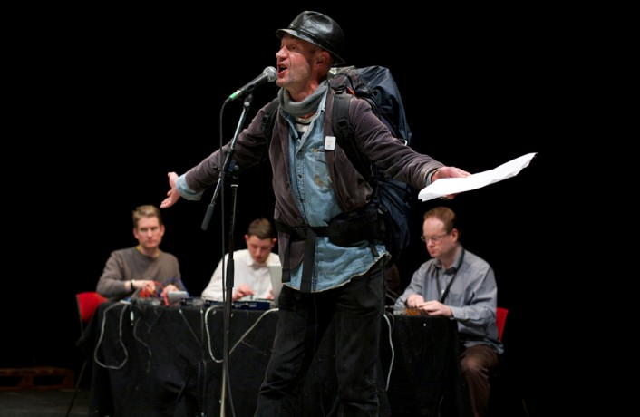 Tam Dean Burn in hat, jacket and rucksack gestures with outstretched arms