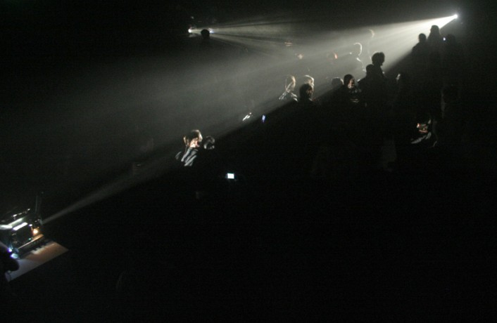 Beams of light fanning out across an audience from different directions