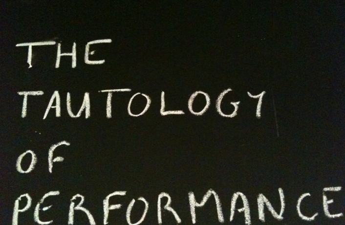 """The Tautology of Performance"" written on a board in chalk"