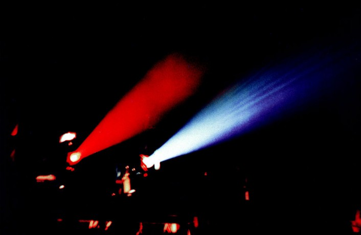 Two shafts of light, one red, one blue come from two 16mm projectors