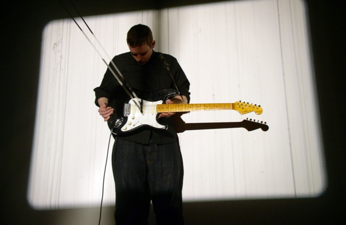 A man holding a guitar with a strip of film in the strings