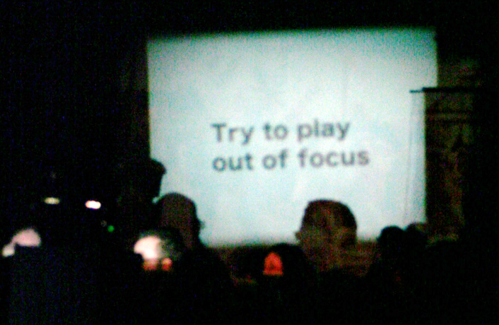 "A blurry projection screen has the words ""Try to play out of focus"""