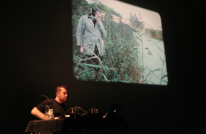 Lee Patterson sitting next to a projection of himself, pensive