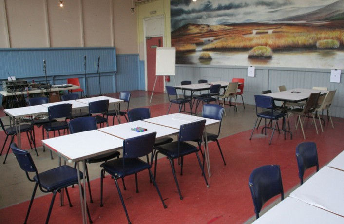 Tables in Kinning Park Complex community centre, a painting on the wall