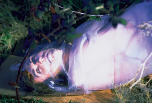 Terre Thaemlitz lies on the ground, wrapped in a plastic sheet, and eerily lit