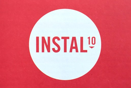 A white circular logo on a red background with the words Instal 10