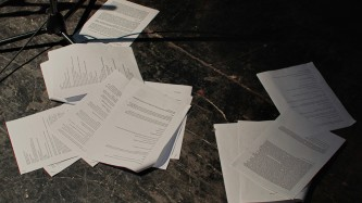 Script papers are strewn across a black floor