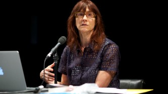 Ann Cvetkovich sitting at a table speaking into a microphone