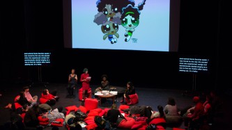 A projection, red cushions, audience members and a discussion