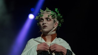 Sgàire Wood on stage in pastoral pagan clothing during Episode 9