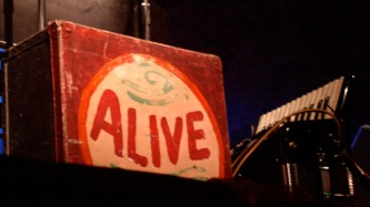 A packing case with the word ALIVE painted on it sits on stage