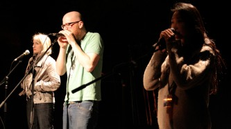Three performers stand and speak and shout into microphones