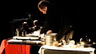 Michael Colligan is hunched over a table of objects and a lump of dry ice