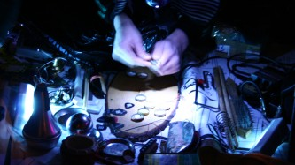 Hands fiddle with items lit by headtorch