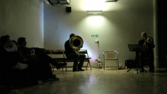 Robin Hayward and Radu Malfatti play brass instruments at the far end of a room
