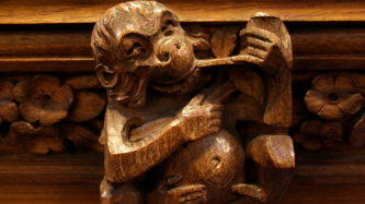 A wooden carved monkey smokes a pipe