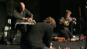 Three men play instruments in various stages of dismantlement