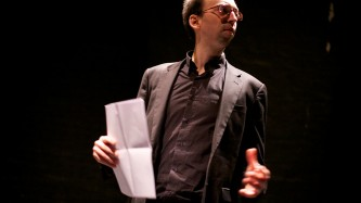 Matthew Saladin wearing a suit gesticulates as he talks and holds a paper