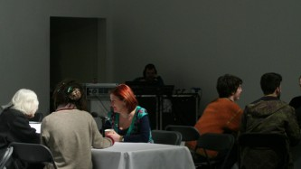 Seated people chat near microphones