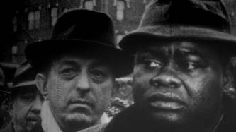 Two men in hats in a black and while film still look warily off screen