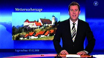 A newsreader in a suit looks to camera as a blue backdrop shows buildings