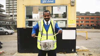 A man in Hi Vis smiles as he plays a snare drum in a car park