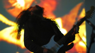 Makoto Kawabata playing electric guitar in front of a projection
