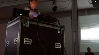 Carsten Nicolai operating some equipment near a projection