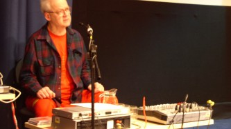 Tony Conrad wearing a shirt and orange t shirt looks forlorn
