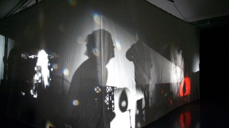 Some figures and equipment casting shadows on a fabric screen