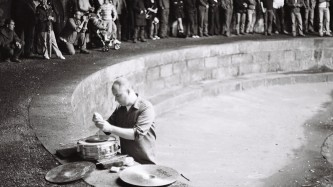 Sean Meehan performing in a on a curved wall before an audience