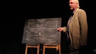 James Whitehead standing by a blackboard
