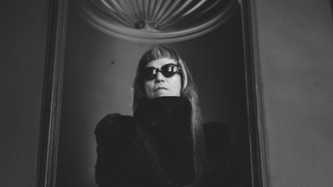 Keiji Haino in a black fur jacket looking straight at camera in front of a wall
