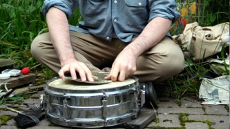 A close up of Sean Meehan's hands as he cracks rosin on a snare drum