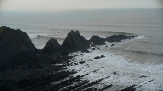 A jagged bluff of rocks juts out into a grey and moody sea as waves lap at shore