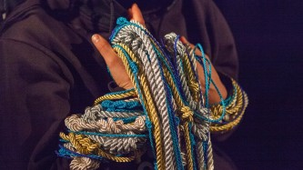 Someone hands are bound in maybe 15 different, irregularly knotted ropes