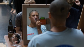 mirrors set up for makeup application with boychild applying makeup in a mirror