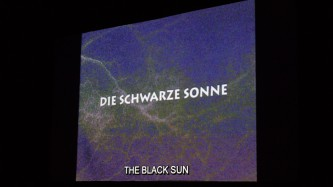 A fuzzy purple and green screen shows the words Die Schwarze Sonne