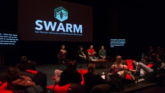 SWARM banner projected, a discussion, audience, red cushions