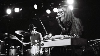 a man playing drums behind a woman playing a pedal steel guitar