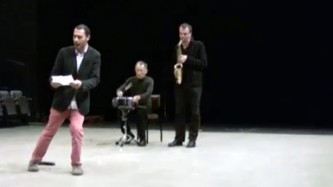 A man in pink trousers makes movements with his legs as two musicians play