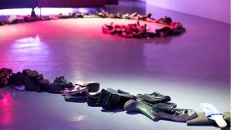 A spiral form made of shoes and boots is laid out on a purple and red lit floor