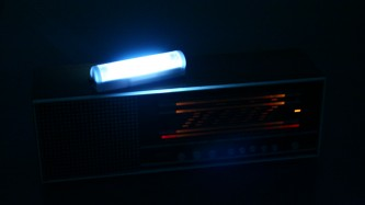 Close up of a radio with a glowing fluorescent tube on top