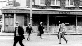 A B and W film still of several people crossing a street in 1960's london