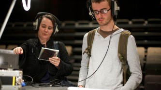 Two people with headphones listen to items in an installation at a large table