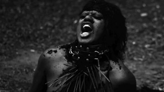 A B&W shot of M Lamar prostrate and seemingly screaming
