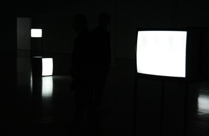 TV monitors in a dark room showing white screens