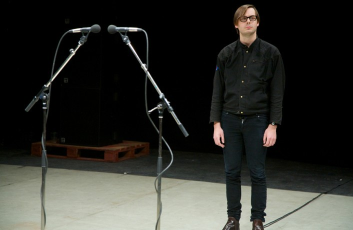 Man in Black clothes standing next to two microphones, staring out
