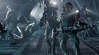 3 people dressed in futuristic armour with guns in a grey tunnel.